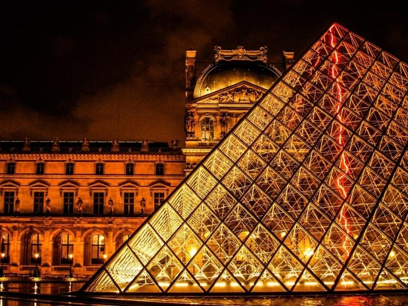 The Louvre pyramid at night in Paris France.